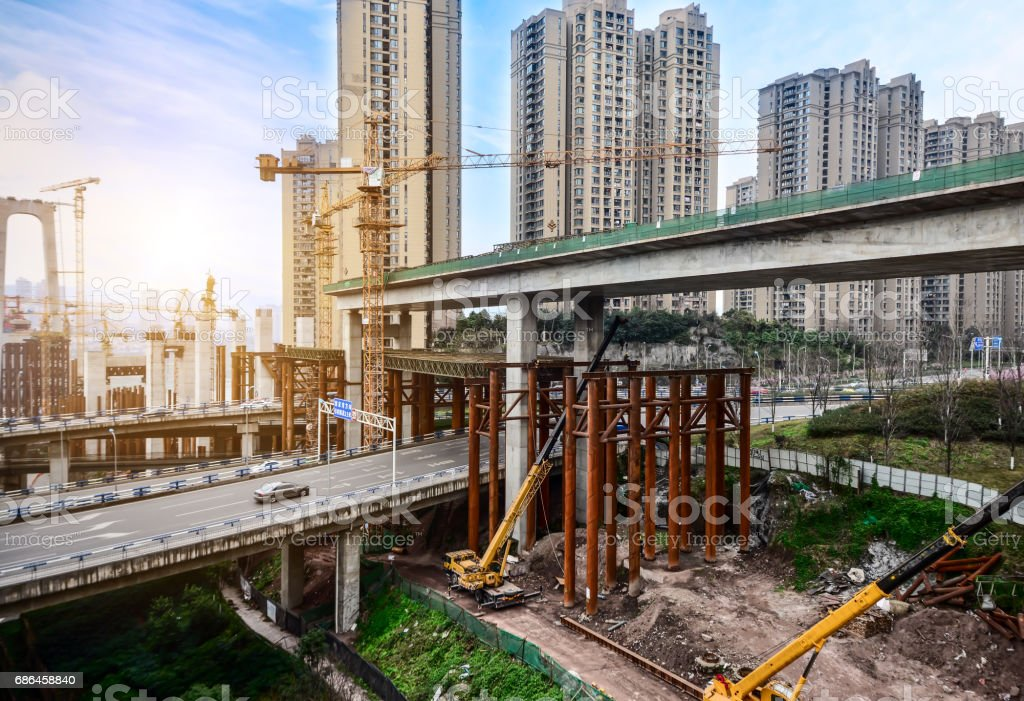 Construction of tall concrete pylon of bridge using tower crane stock photo