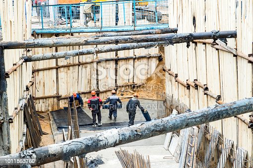 istock Construction of the earth tunnel, preparation of the frame for pouring concrete. People working in overalls unwound cover synthetic material Moscow, may, 2018 1011863760