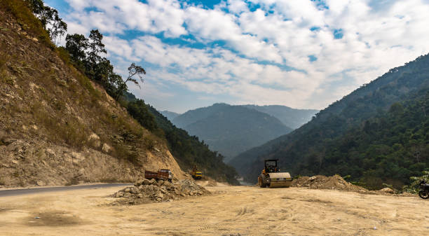 Construction Heavy Earth Moving Machineries and equipments are using to construct new Road on hillside area. compactor stock pictures, royalty-free photos & images