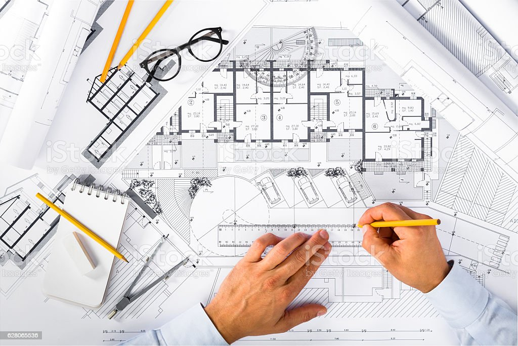 Construction plans and Male Hands drawing on blueprints – Foto
