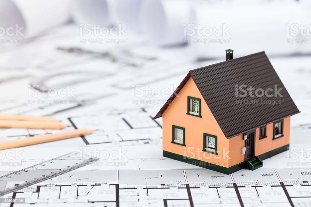Construction plans with drawing tools and House Miniature on blu stock photo