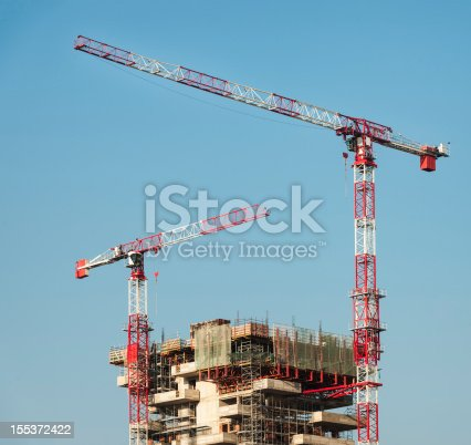 Construction cranes at a high-rise building project.