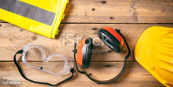 istock Construction safety. Protective hard hat, headphones and glasses on wooden background, copy space, top view 1031809378