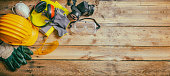 istock Construction safety. Protective hard hat, headphones, gloves and glasses on wooden background, banner 1081887350