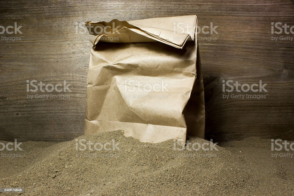 Construction sand and paper bag on wooden background stock photo