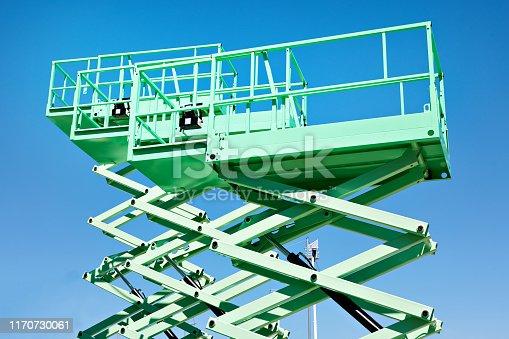 Construction scissor lifts on sky