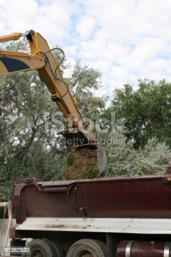 Arm and bucket of a trackhoe moving dirt into a dump truck.
