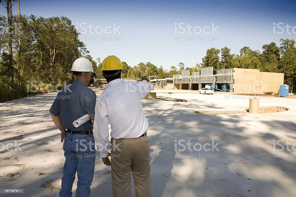 Construction site and architects discussing progress royalty-free stock photo