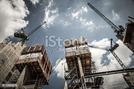 Low angle color image depicting a construction site in London, UK. A housing development is in the process of being created, and multiple cranes are hoisting materials into place. Beyond the cranes and construction equipment is a dazzling sky and cloudscape. Lots of room for copy space.