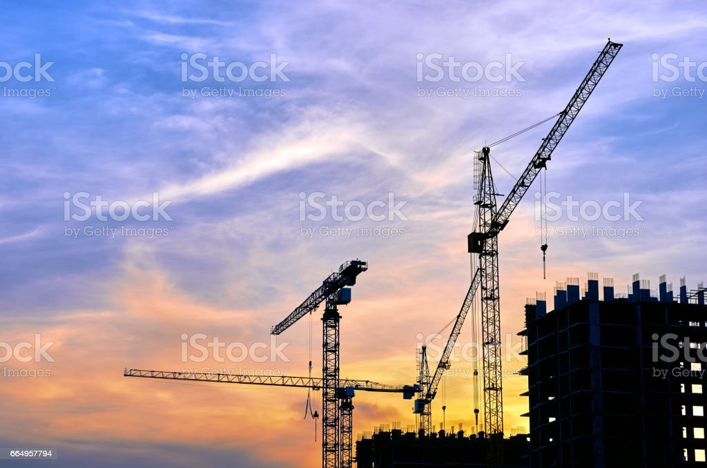Construction site at dusk evening yellow back light, silhouette cranes, sunlight stock photo