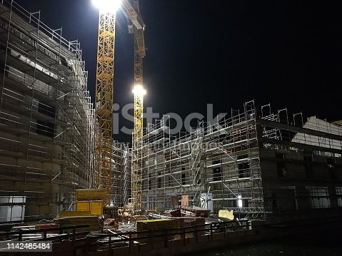 a construction site by night illuminated by floodlight.