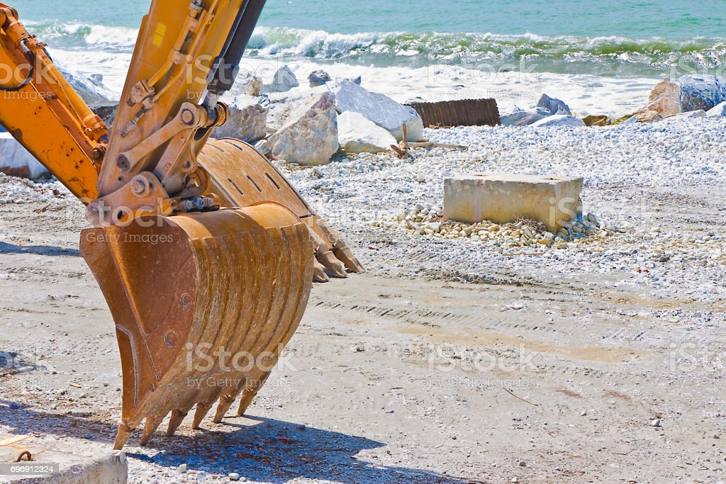 Construction site by the sea for the realization of an embankment with excavator's bucket on background stock photo