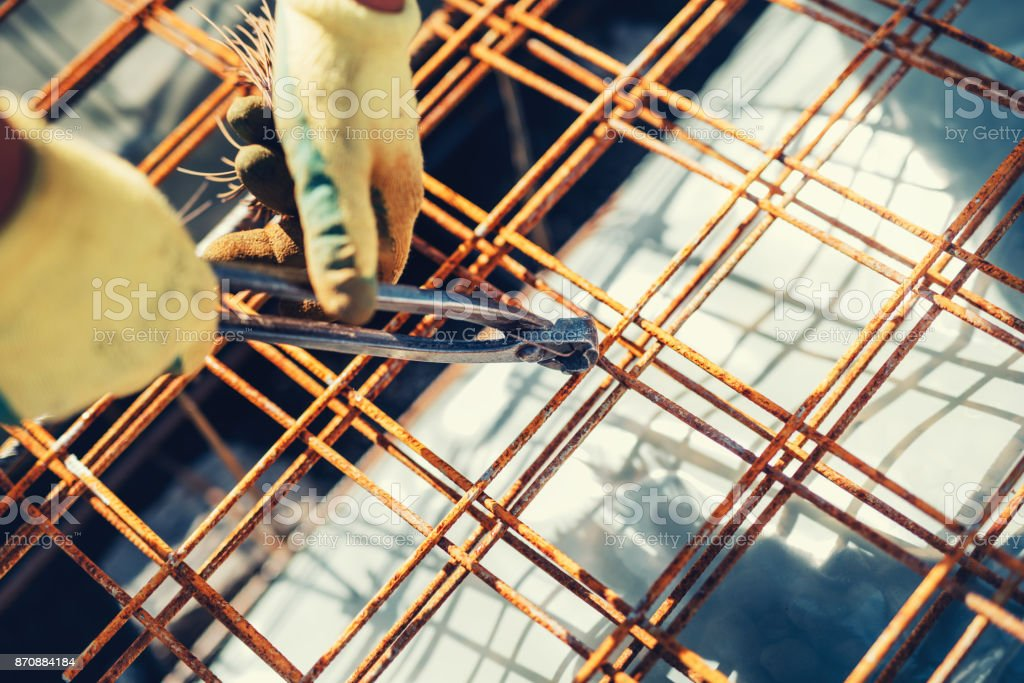 Construction site details with worker using wire rod and pliers for securing reinforcement steel bars on house building stock photo