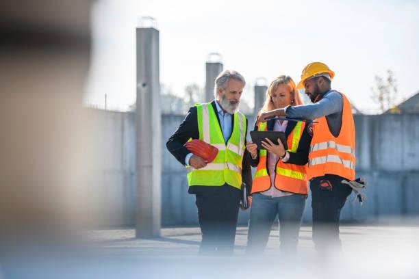 Construction Site Development Team Checking Digital Tablet stock photo