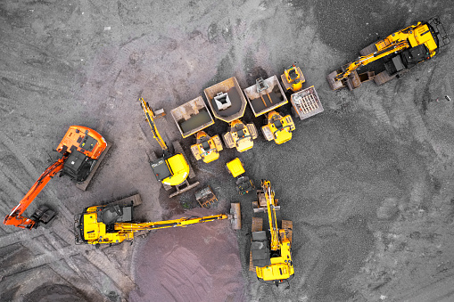 istock Construction site diggers yellow and orange aerial view from above 1164484534