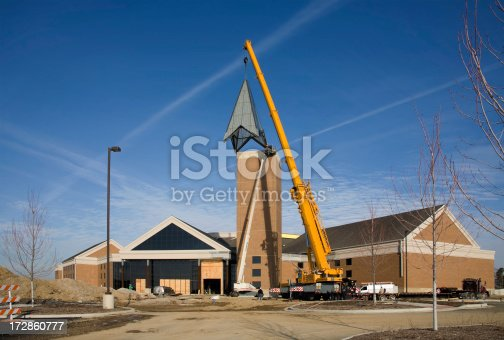 a crane lifts the steeple to the top of a tower on a newly built church building