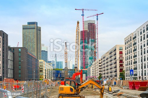 Excavator, cranes and construction equipment at construction site in downtown at street with buildings and skyscaraprers of modern architecture, Frankfurt am Main, Germany
