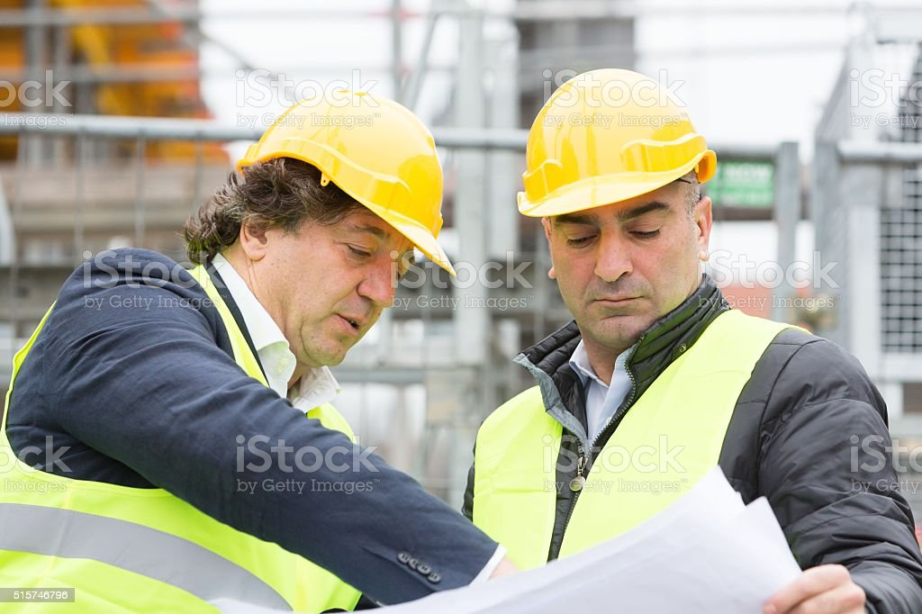 Construction site manager explaining blueprints stock photo