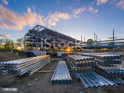 Construction site with steel flooring in front of a  partially erected building at sunset