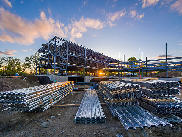 Construction site of a building with supplies Construction site with steel flooring in front of a  partially erected building at sunset girder stock pictures, royalty-free photos & images