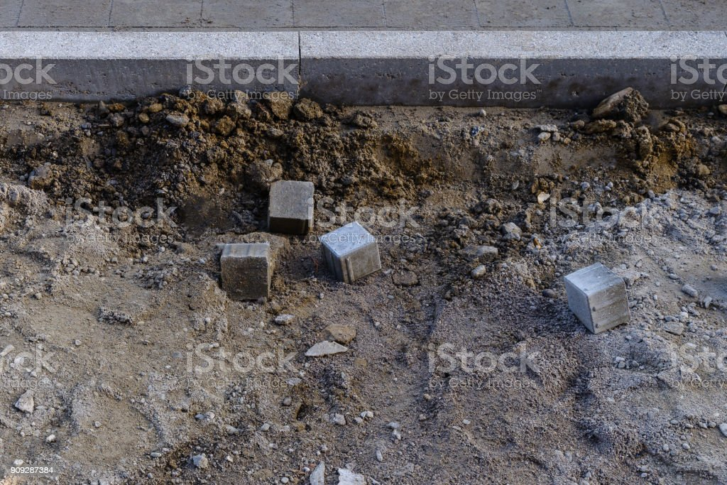 Construction site of a sidewalk with single paving stones stock photo