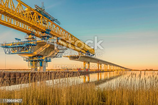 Construction site of Crown Princess Mary bridge over the Roskilde firth in the sunset, a huge yellow crane reflecting in the water. Frederikssund, Denmark, Mars 12, 2019