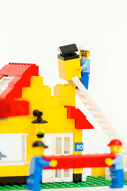 construction site of lego, workers build a house - lego house stock photos and pictures