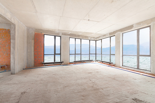 Interior in progress with sea view large panoramic windows and red brick wall, panel floor. Built structure construction site of residential apartment building room.
