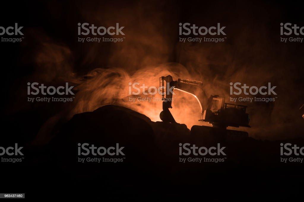 Byggarbetsplatsen på en stadsgata. En gul digger grävmaskin parkerad under natten på en byggarbetsplats. Industriella konceptet bordsdekoration på mörk dimmigt tonad bakgrund - Royaltyfri Anläggningsmaskin Bildbanksbilder