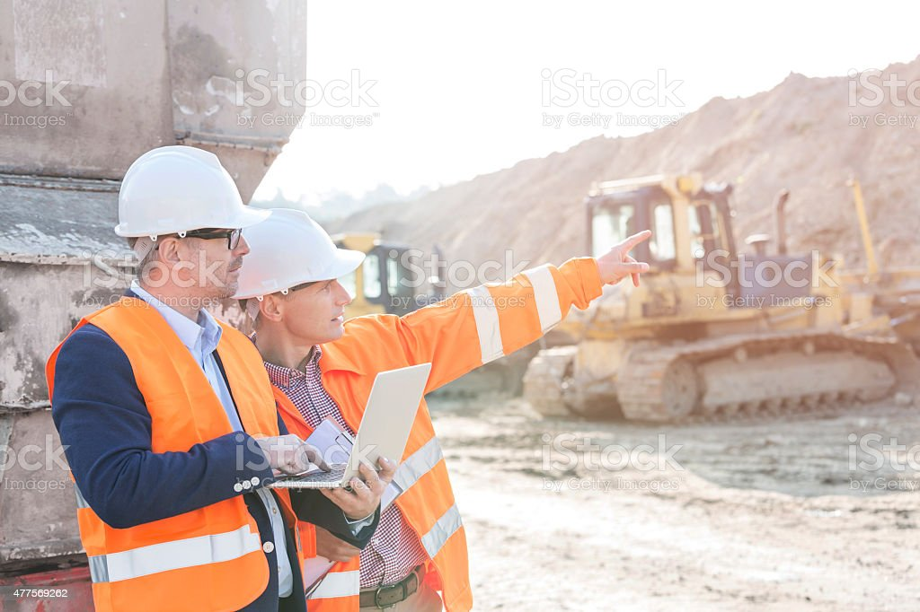 Construction Site Supervisor showing something to coworker holding laptop at construction site 2015 Stock Photo