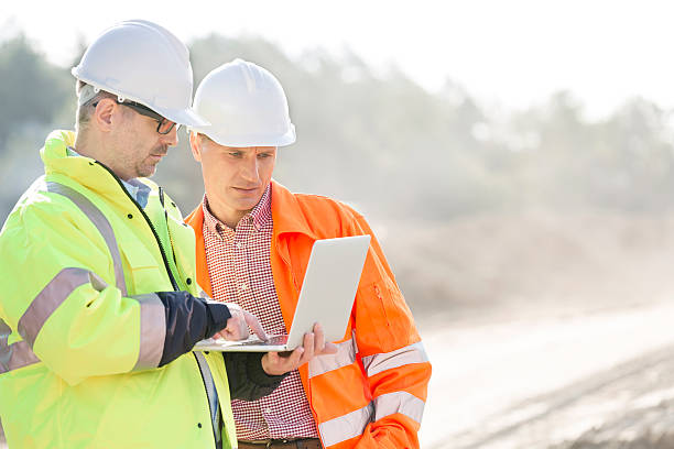 Construction Site Supervisors using laptop at construction site reflective clothing stock pictures, royalty-free photos & images