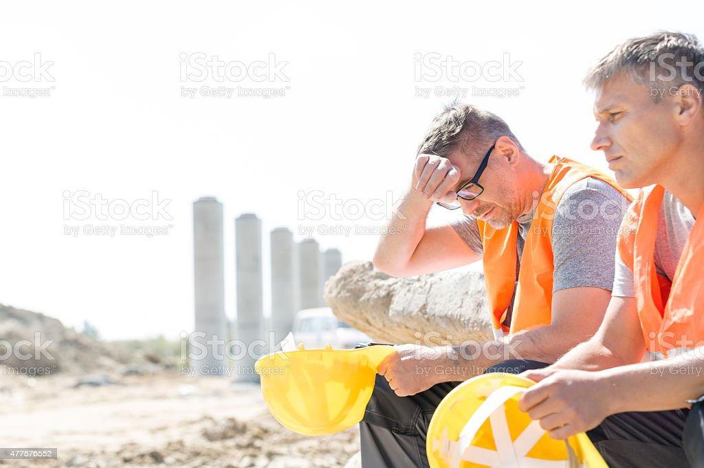 Construction Site Tired supervisor sitting with colleague at construction site 2015 Stock Photo
