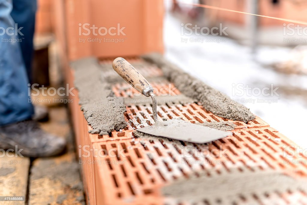 construction site, trowel, putty knife on top of brick layer stock photo