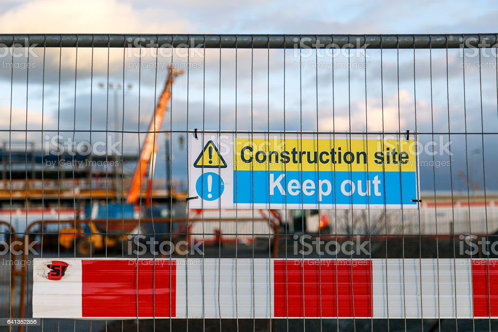Construction site warning signs in yellow and blue instructing people to Keep Out. stock photo
