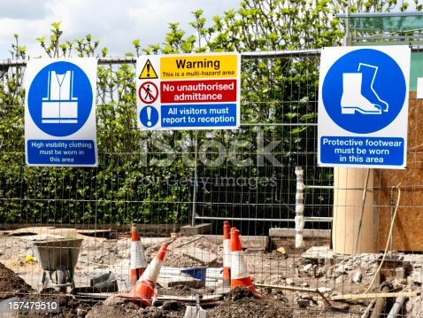 A variety of signs on a construction site fence.