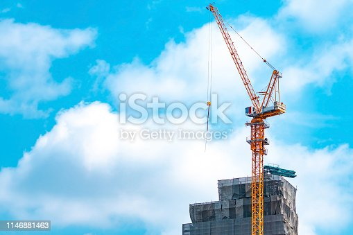 istock Construction site with crane and building. Real estate industry. Crane use reel lift up equipment in construction site. Building made of steel and concrete. Crane work against blue sky and white cloud 1146881463