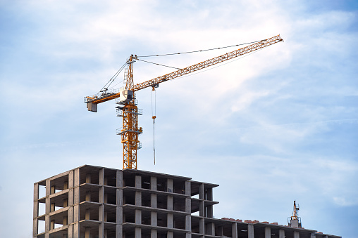 Construction site with crane at cloudy blue sky