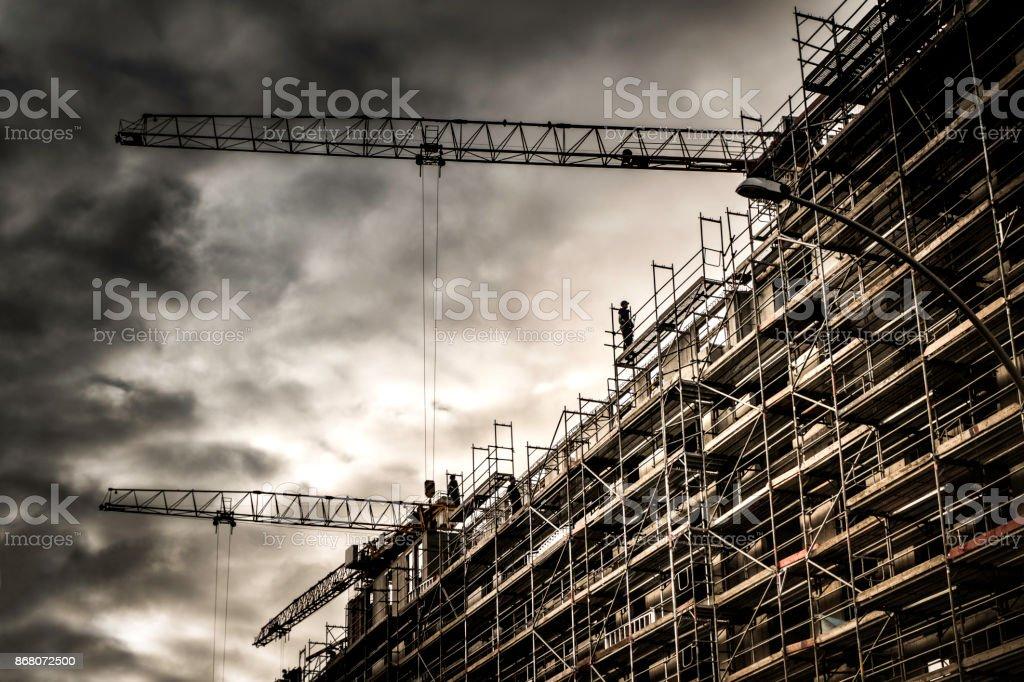 Baustelle mit Kränen und dramatischer Himmel – Foto