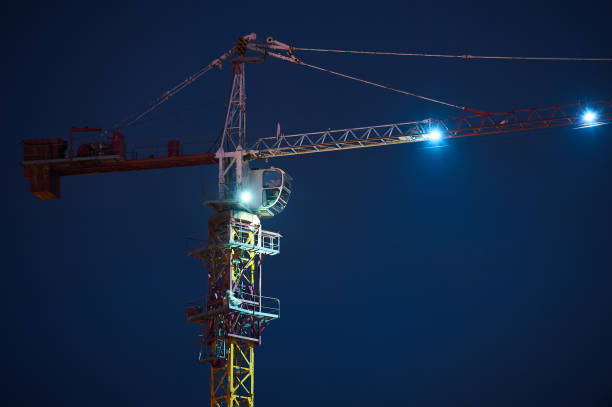 Construction site with cranes on dark sky background at night stock photo