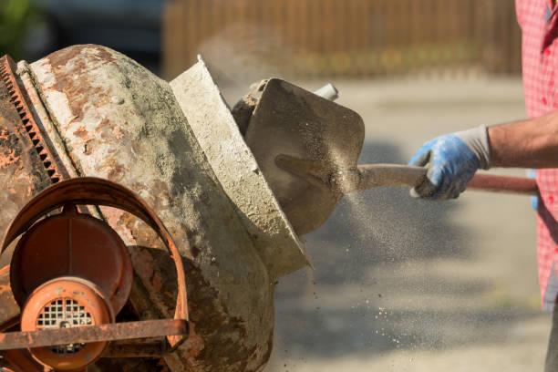 bouw site werk met betonmixers en kruiwagens - kruiwagen met gereedschap stockfoto's en -beelden