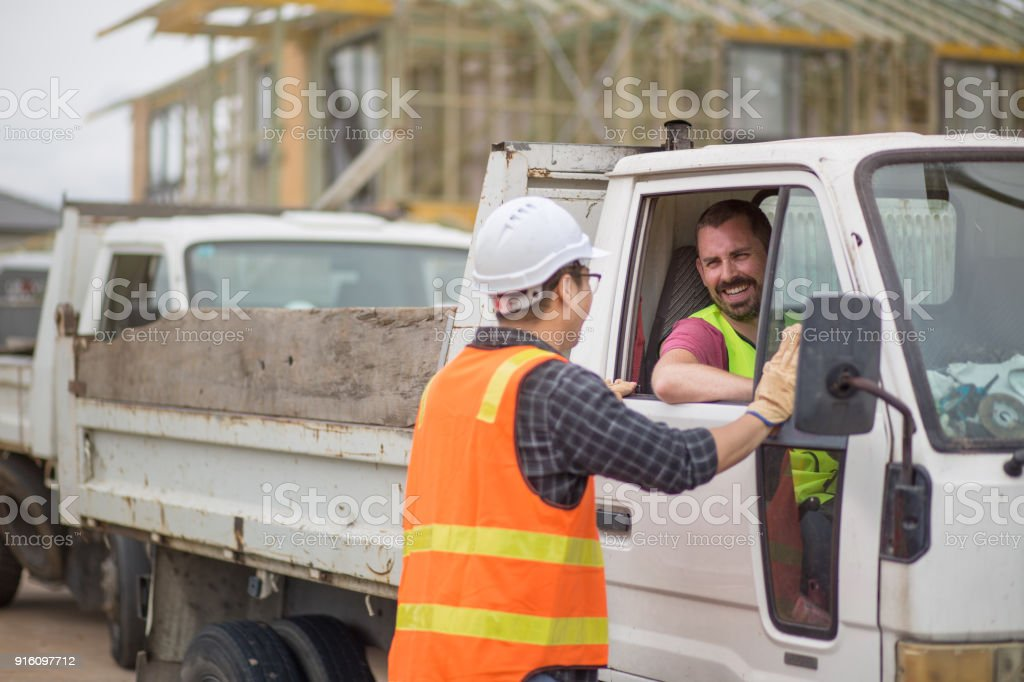 Construction site workers talking before leaving building site stock photo