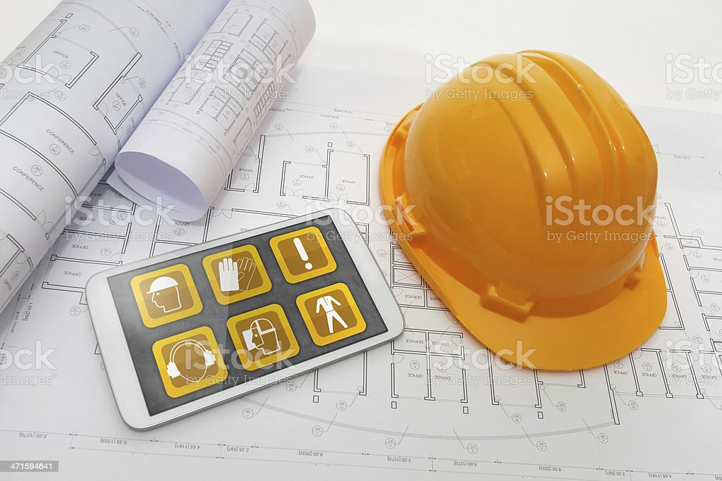 Construction site workplace safety plan: hardhat, blueprints, gloves, interactive symbols stock photo