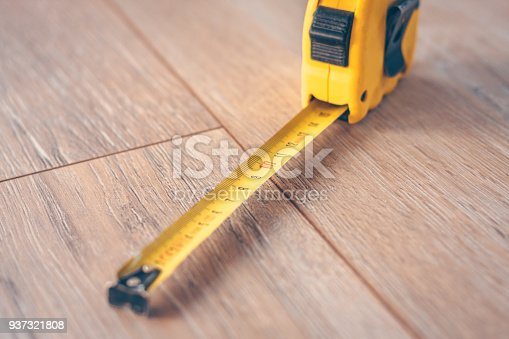 Construction tape measure on a wooden floor