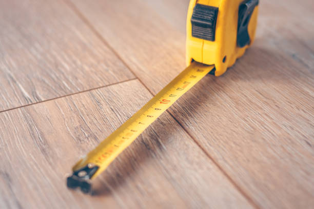 Construction tape measure on a wooden floor stock photo