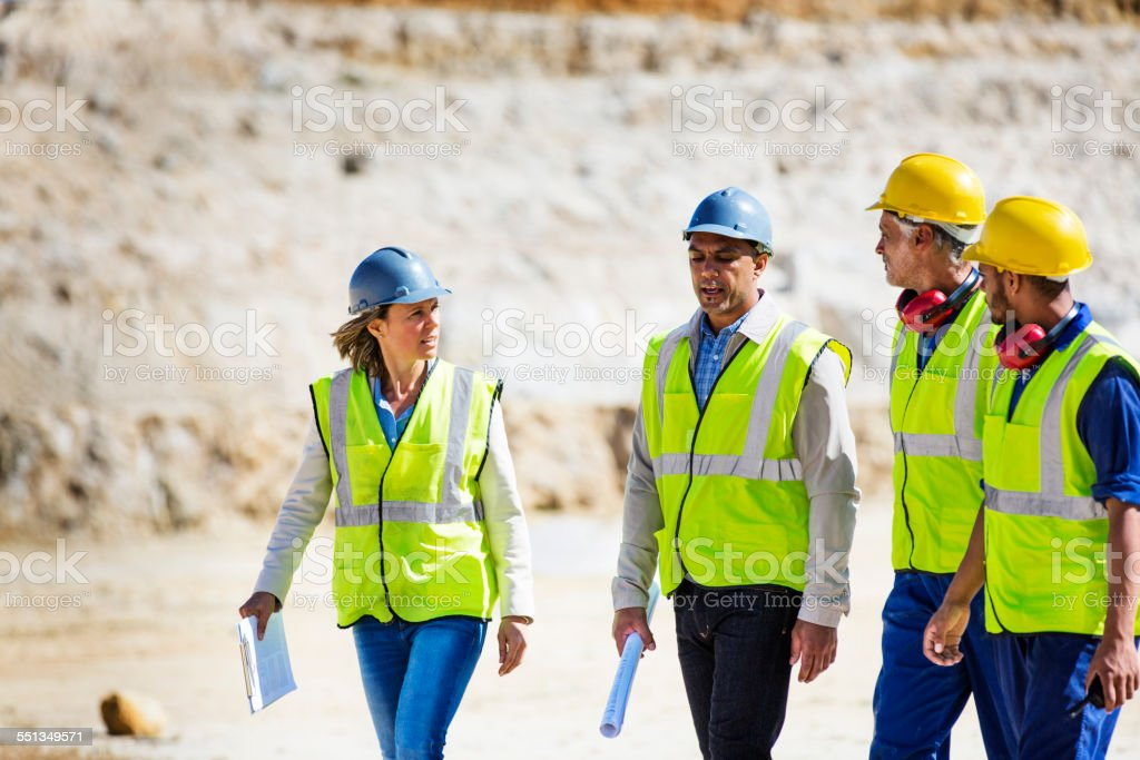 Construction team discussing at quarry stock photo