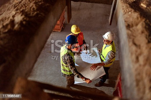Photo of one Engineer showing blueprint to two workers. Three construction engineer working in construction site, construction engineering conceptual.