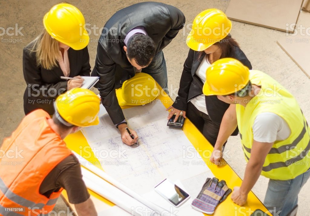 Construction team going over building blueprints stock photo
