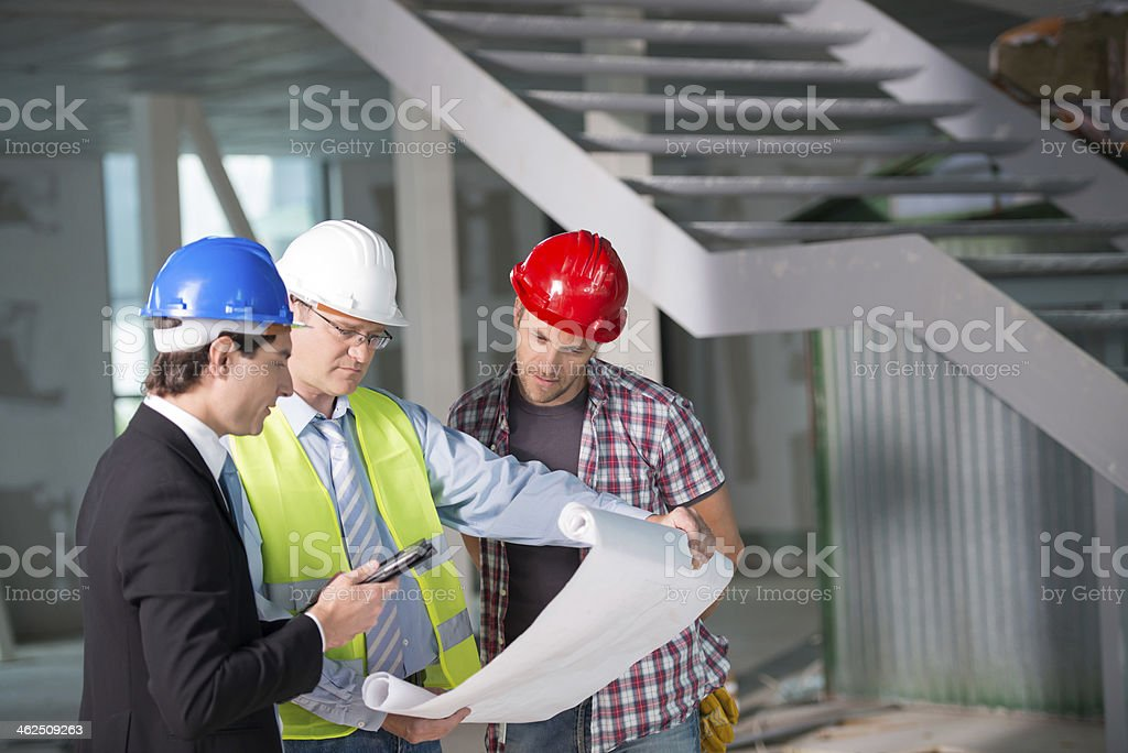 Construction team reviewing blueprints together stock photo