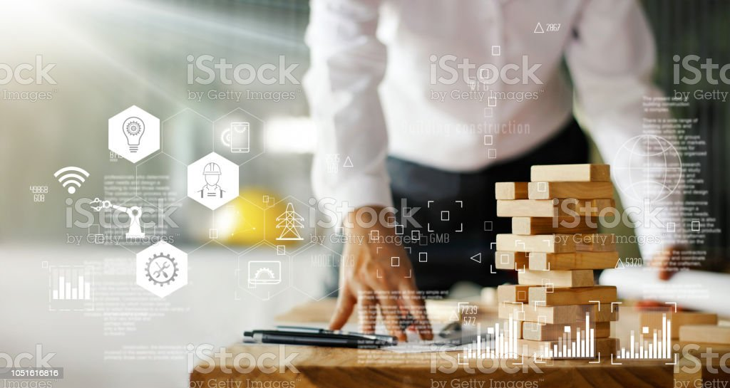 Construction technology concept. Engineer working on wooden plan model building and icon network connection, intelligence technologies and innovation. stock photo
