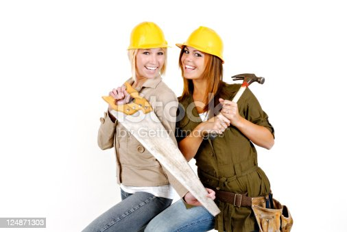 Two Women. Yellow Hard Hats, Hammer, Saw. Expressive Smiles and Wide Eyed Look! Dressed in Jackets. One Blond and One Red Head/Brunette.